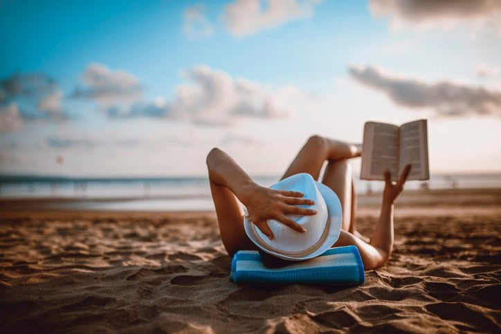 A woman lying on the beach reading a book.