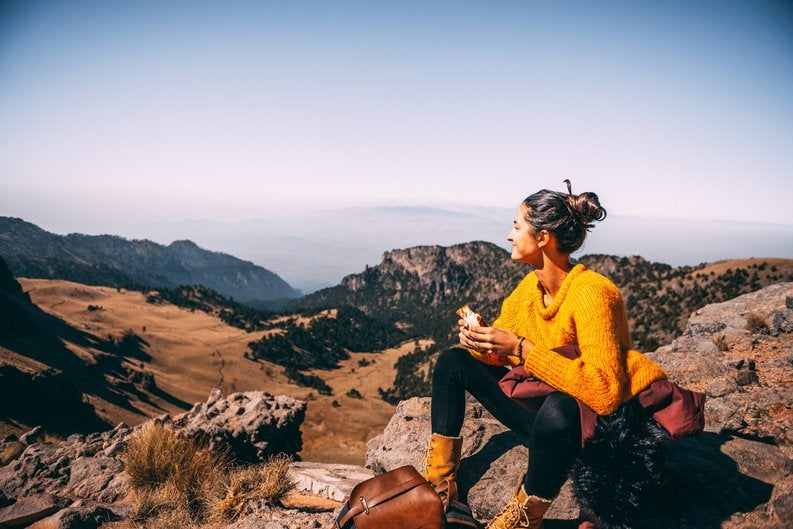 A female hiker taking a break for lunch on top of a hill and admiring the view.