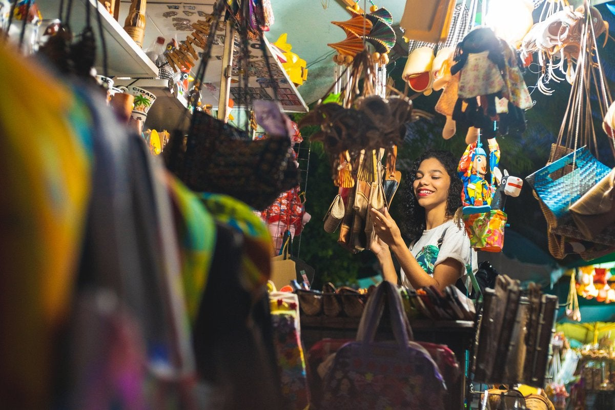 A young woman happily looking at handmade items in the booth at a craft market.