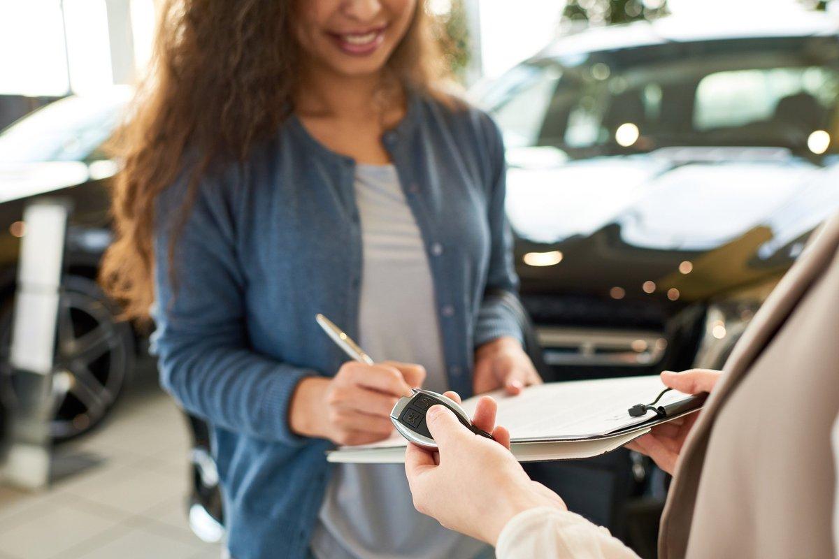 woman signing car paperwork