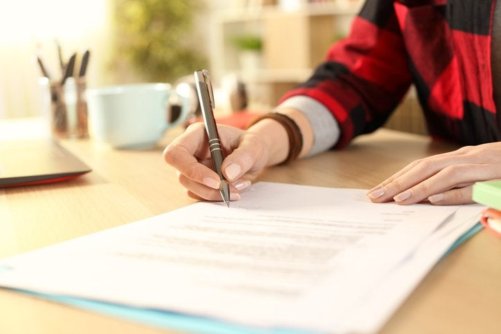 A woman's hands signing paperwork on a desk in a sunny business office.