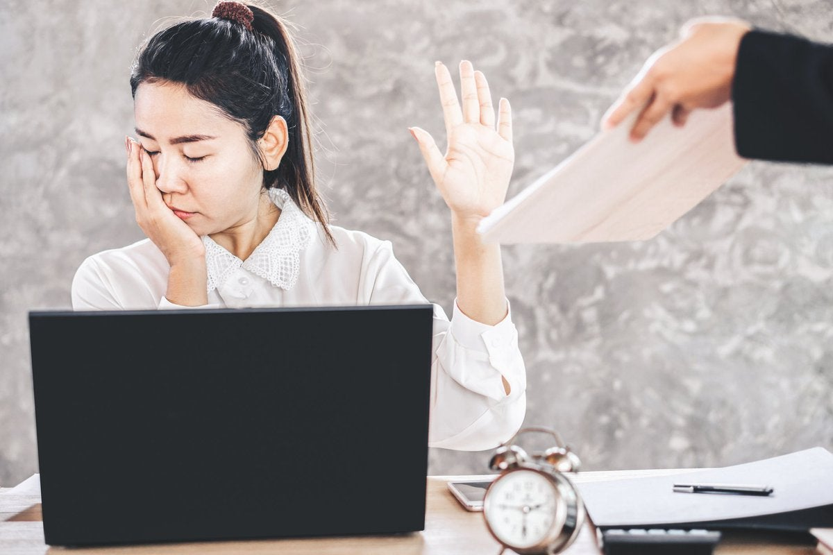 woman sitting at desk looking away and holding up her hand as a coworker tries to hand her a document.