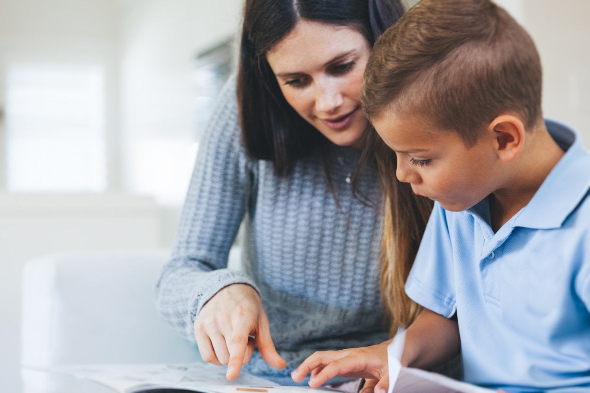 A woman tutoring a young boy.
