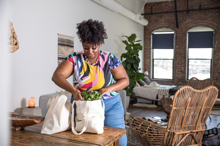 A woman unpacking grocery bags in her home.