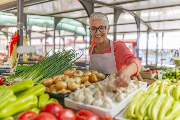 A woman standing behind her food stall at a farmers market and rearranging vegetables.