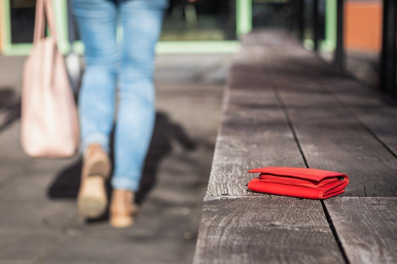 woman walking away from bench with wallet sitting on it