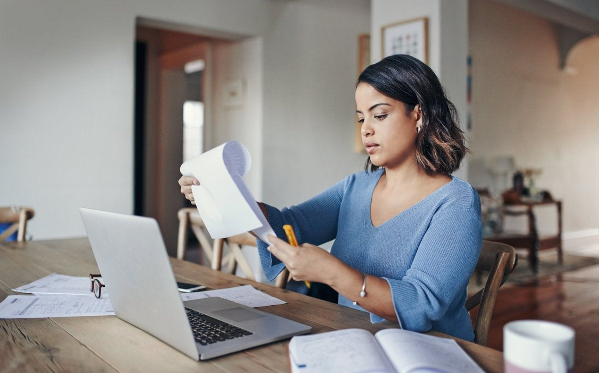 A woman looking over her bills with a laptop and notepad at her kitchen table.