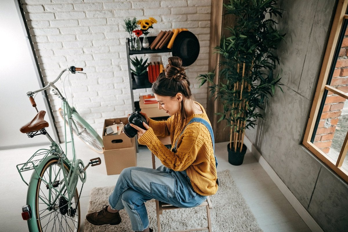 A woman taking photos of her bike and other items in her apartment.