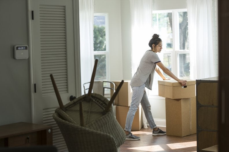 A woman looking unsure while moving boxes into a new house.