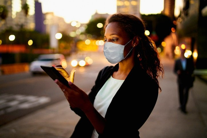 A woman in a mask looks at her phone on a street at dusk.