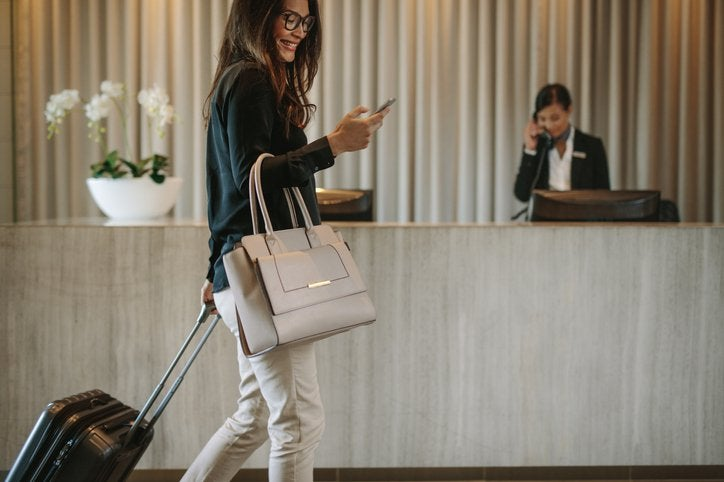 A smiling woman talking on her phone while walking with her suitcase into the lobby of a hotel.