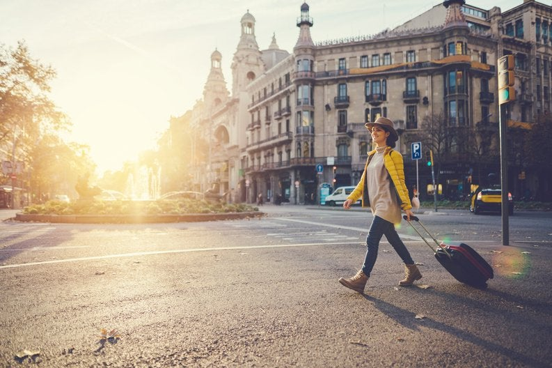 A woman with a suitcase crossing a street in a foreign city with the. sun behind her.