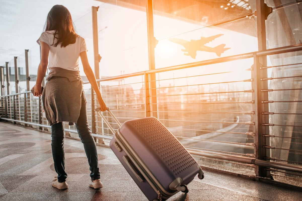 A female traveler walking through a sunny airport with her suitcase.