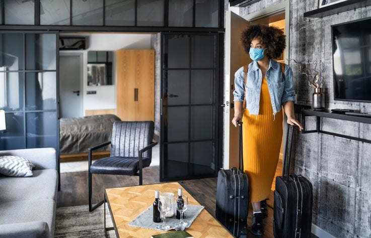 A woman wearing a medical mask and wheeling her two suitcases into a nice hotel room.