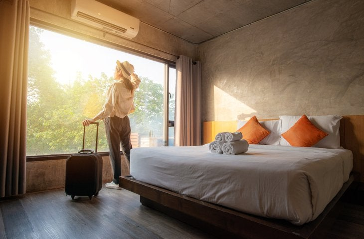 A woman standing next to her suitcase and looking out the window of her sunny hotel room.