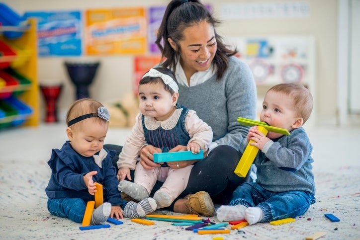 A woman sitting on the floor of a daycare room with three babies on her lap.