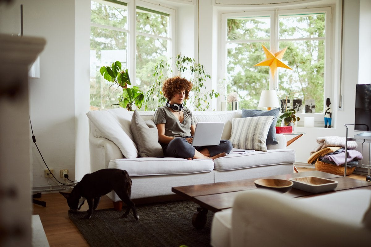 A woman sitting cross-legged on the couch working on her laptop.