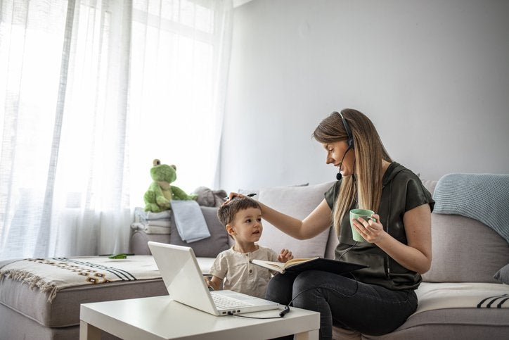 A woman working from her couch with a laptop and phone headset while resting her hand on her young child's head.