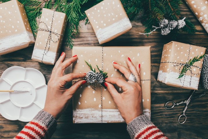 A woman's hands wrapping gifts with brown paper and pine tree trimmings.