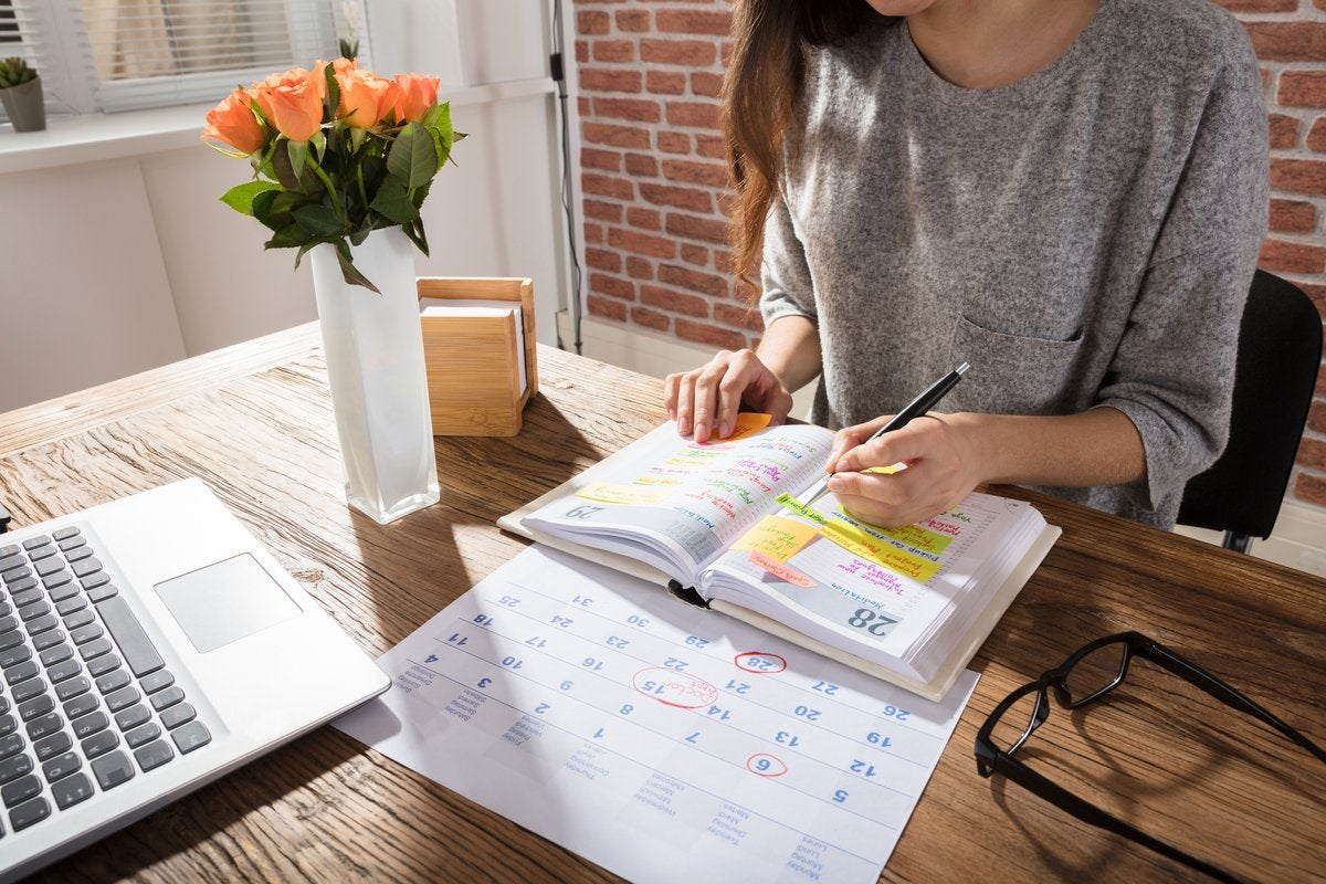 A women sitting at a sunny desk with a laptop, calendar, and planner.