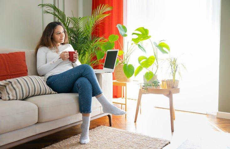 Una donna sul divano con una bevanda calda e un laptop.
