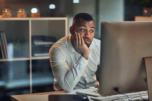 A worried-looking man staring at his computer with his chin in his hand.
