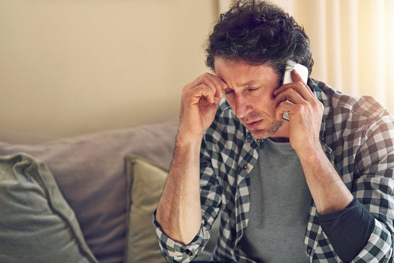 A man looking worried while on a phone call sitting on his couch.