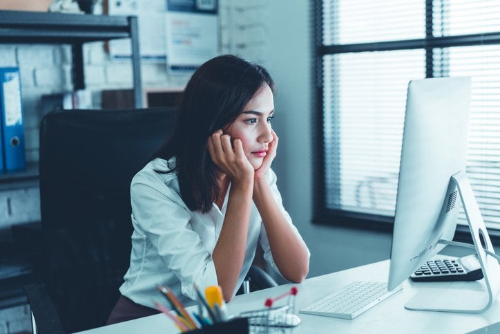 A woman sitting at a desk in front of a computer and staring into space with her chin resting in her hands.