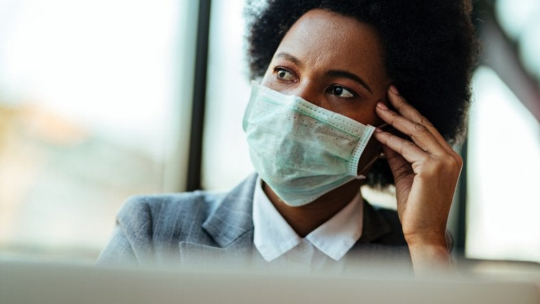 A worried woman wearing a medical mask and resting her head on her hand.