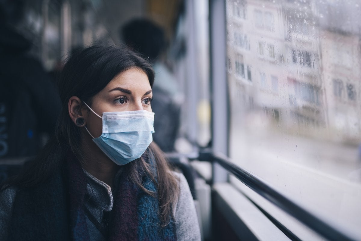 A worried-looking woman wearing a protective mask while riding the bus.