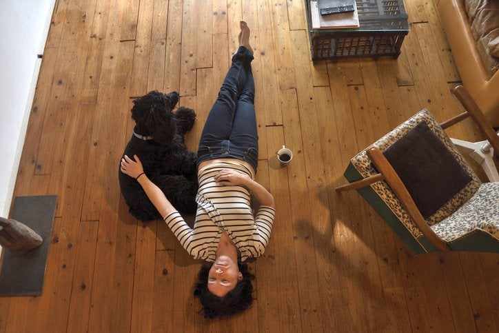 Upset women laying on the wood floor of her living room and petting her dog.