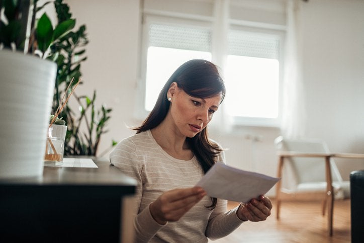 A worried-looking woman reading a letter in her home.