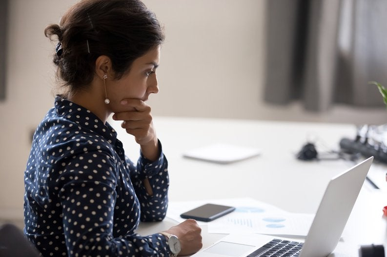 A worried woman with her hand on her chin sitting at a desk with papers and her laptop.
