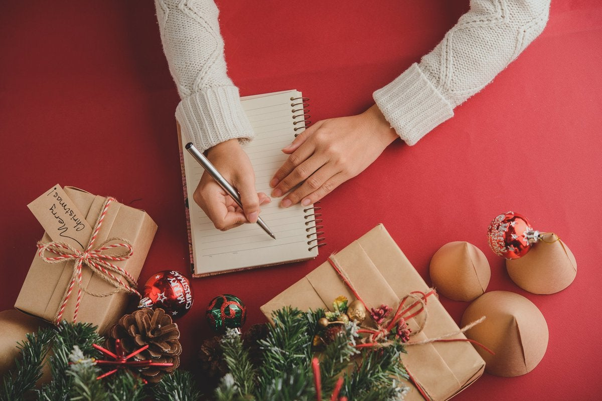 A woman writing a to-do list next to wrapped gifts.