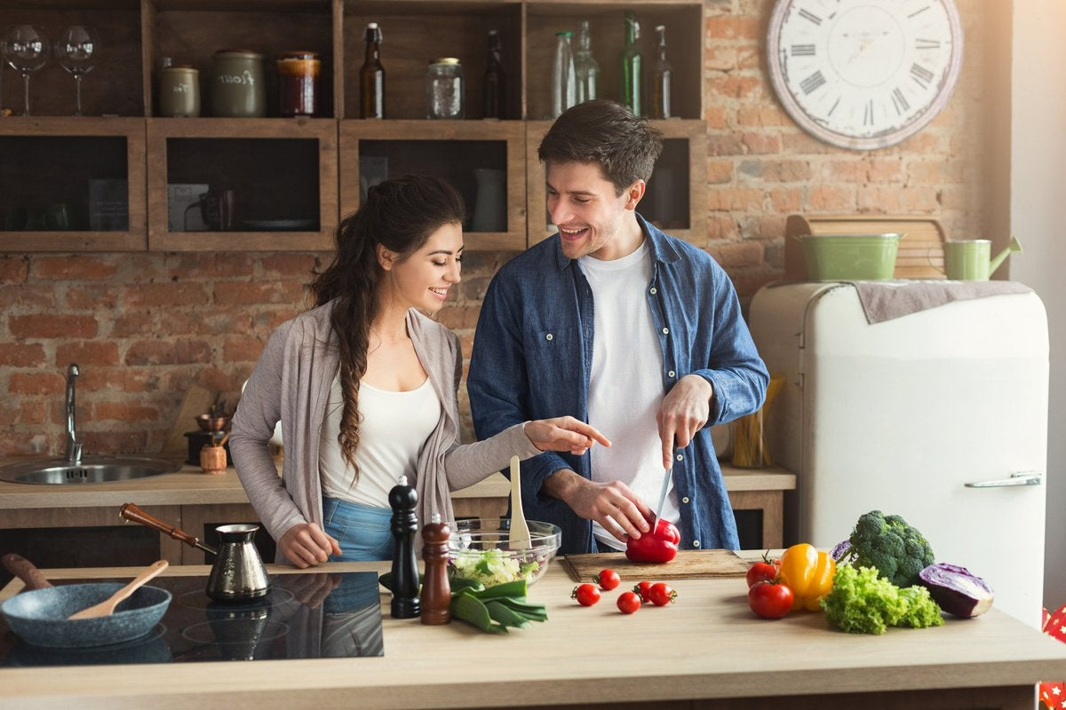 Smiling young couple cooking in kitchen