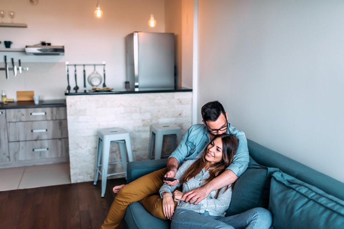 A smiling couple cuddles on the couch in their studio apartment while watching TV.