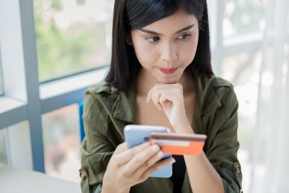 young woman holding credit card and smartphone and thinking with chin on fist