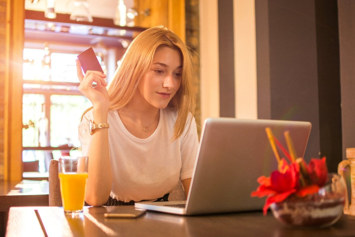 A young woman sitting at a sunny dining room table in front of her laptop and holding a credit card.