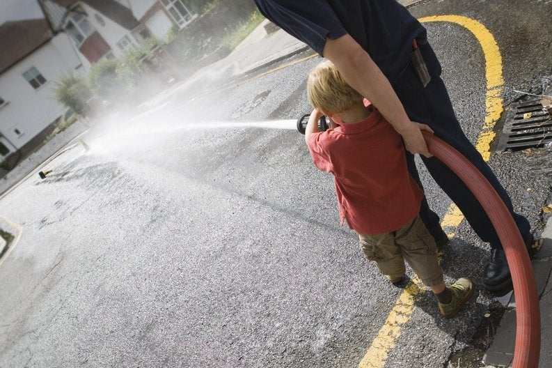 A young boy and a fireman practicing how to use a fire hose.