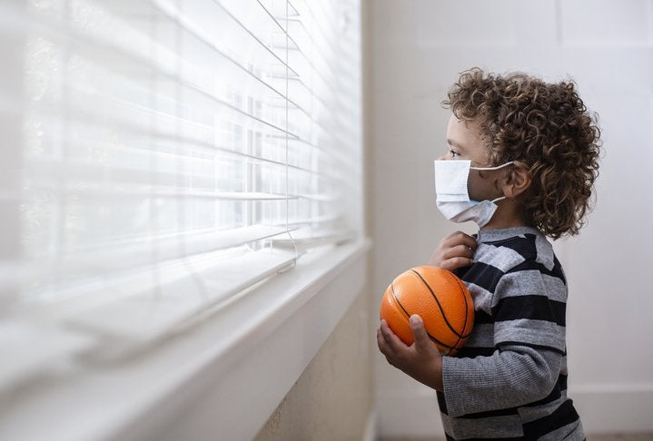 A young boy holding a small basketball and wearing a medical mask while looking forlornly out the window.