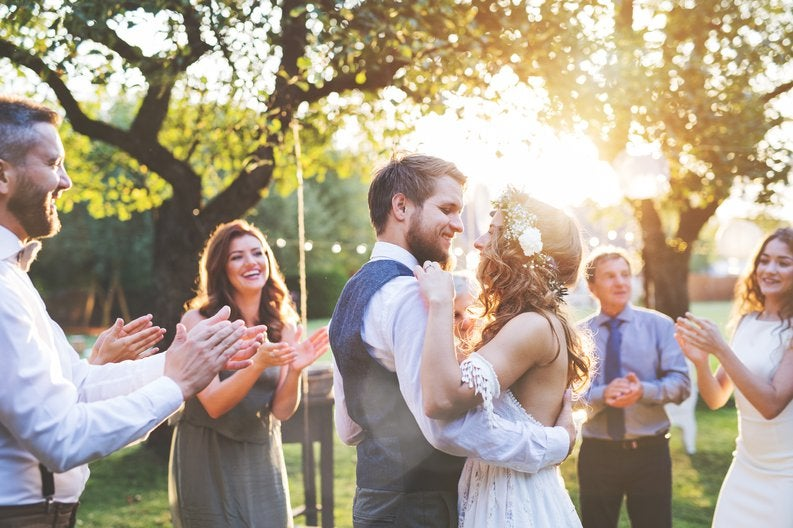 young bride and groom hugging in a backyard surrounded by friends