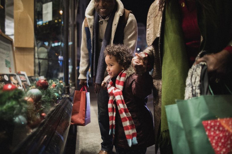 A young child holding hands with his parents and looking at a holiday window display.