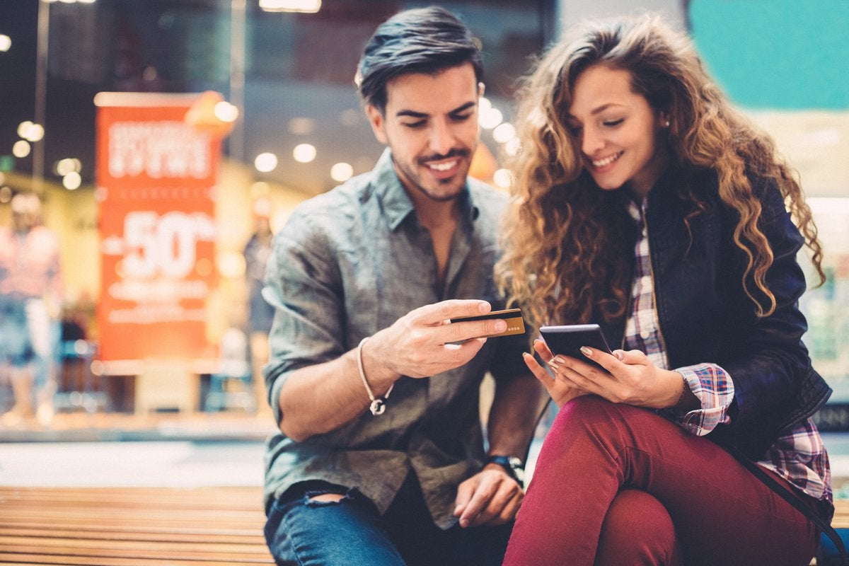 A young couple sitting on a bench at a mall with a phone and credit card in their hands.