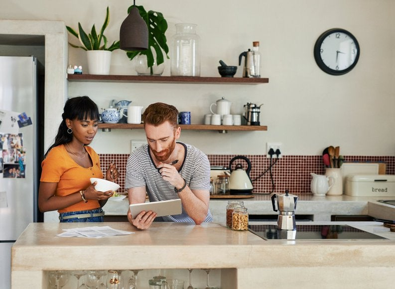 A young couple standing in their kitchen and looking things up on a tablet.