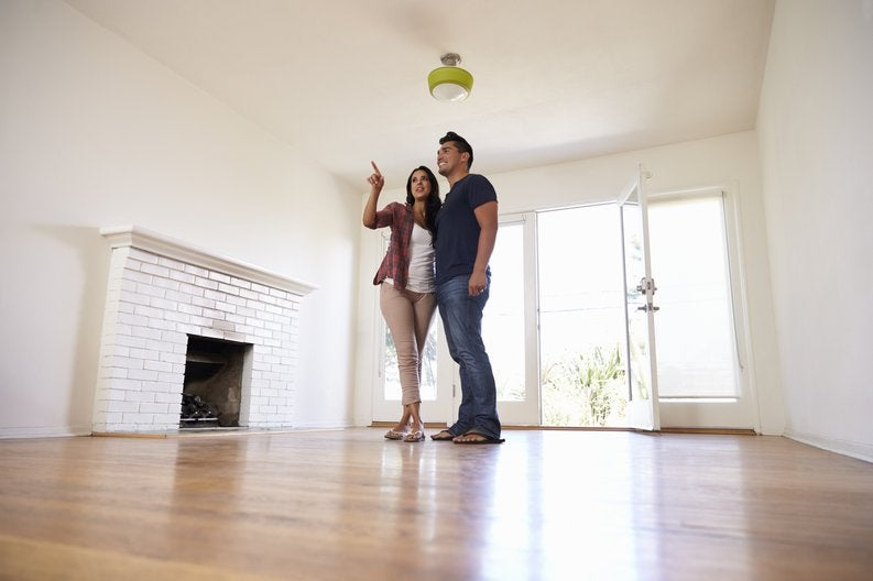 A young couple walking through an empty living room on a house tour.