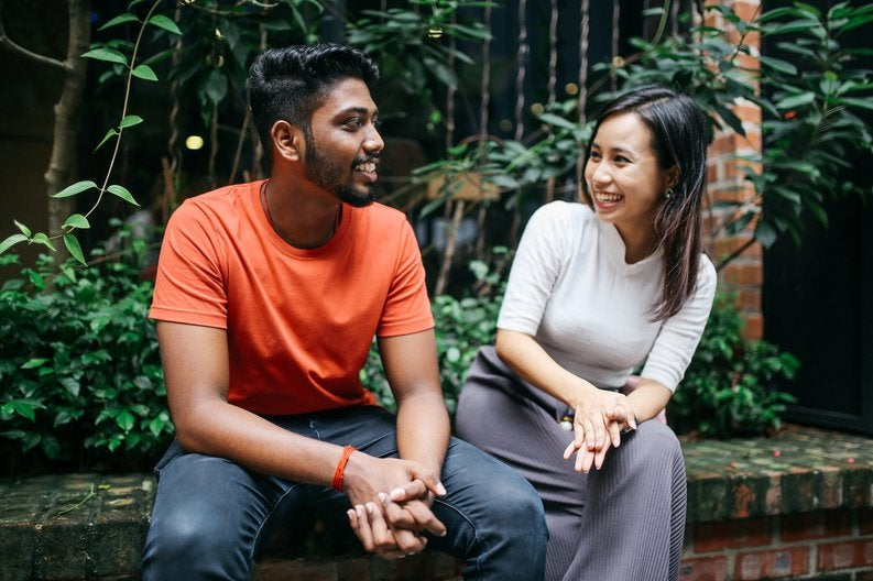 A young couple smiling and chatting while sitting on a brick ledge in front of green bushes.