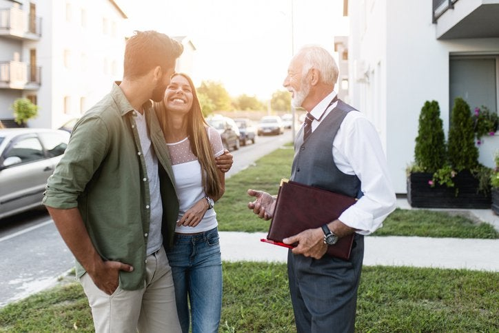 A young couple smiling while talking to their realtor outside a home for sale.