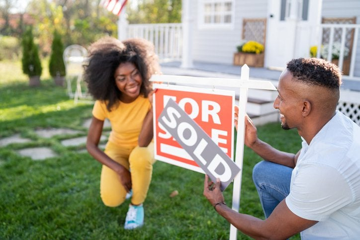 A smiling young couple placing a Sold sign on the For Sale sign in front of their new home.