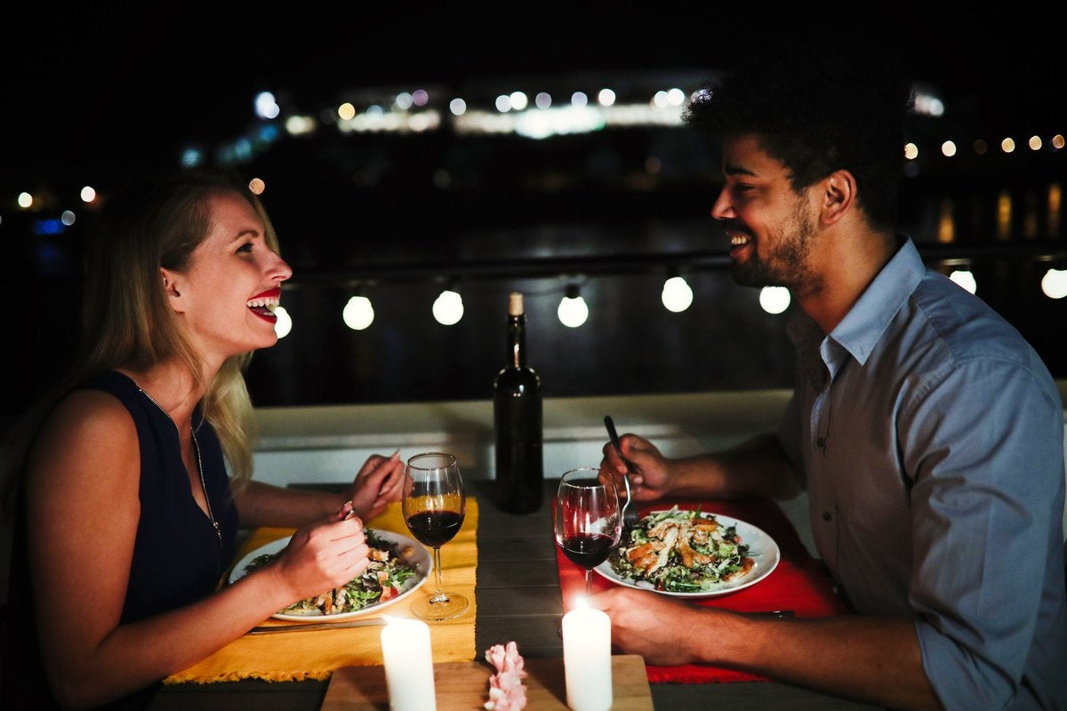 Young man and woman sitting at table eating dinner and laughing.