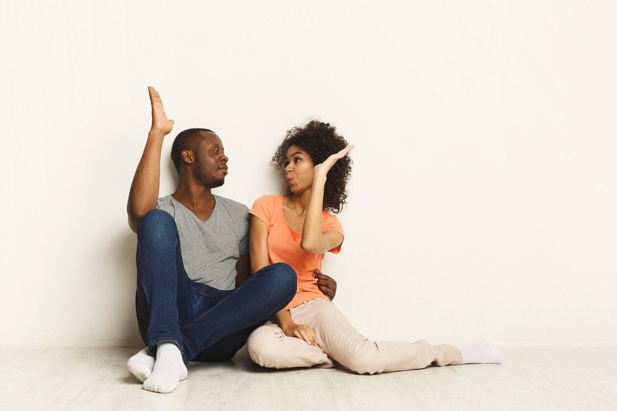 young man and woman sitting next to each other on the floor and giving each other a high five.